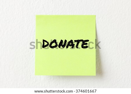 Yellow note paper with words Donate on the white wall