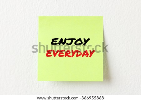 Yellow note paper with words Enjoy everyday on the white wall