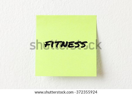 Yellow note paper with words Fitness on the white wall
