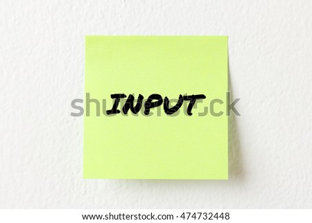 Yellow note paper with words Input on the white wall
