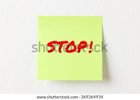 Yellow note paper with words Stop on the white wall