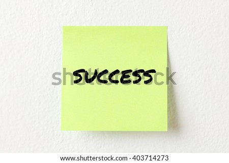 Yellow note paper with words Success on the white wall