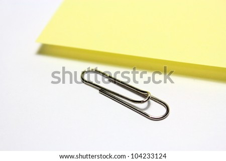 Yellow note with clip on white background - stock photo