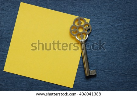 Yellow note with vintage key on dark background