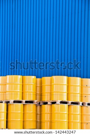 Yellow oil drums and a blue factory cladding