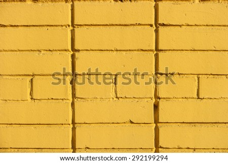Yellow old painted grungy brick wall texture - stock photo