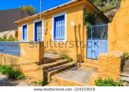Yellow old typical house with blue windows and shutters in Assos village, Kefalonia island, Greece - stock photo