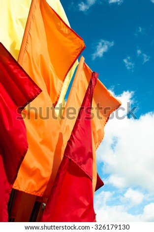 Yellow, orange and red blank flags against the sky closeup view