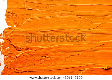 yellow-orange brush strokes of oil paint on the palette - stock photo