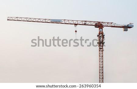 yellow/orange hoisting crane on the sunset background - stock photo