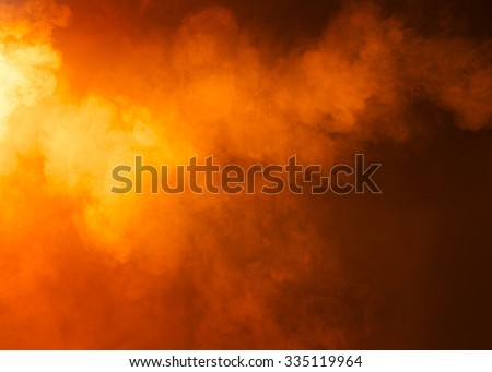 Yellow/Orange mysterious fog photographed on a black background. Ideas as a background texture or overlay. Bright light coming from the left of the image.  - stock photo