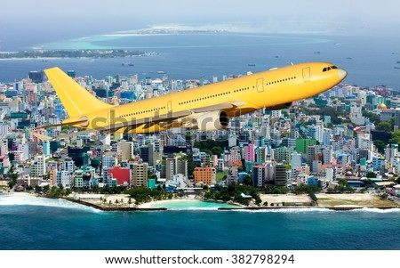 Yellow / Orange plane. Aircraft flying over the city and ocean. - stock photo