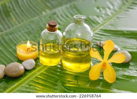 Yellow orchid and stones ,oil with burning candle on wet banana leaf