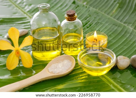 Yellow orchid and stones, oil with burning candle on wet banana leaf  - stock photo