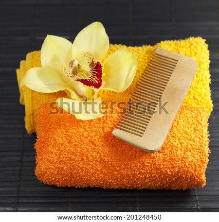 Yellow orchid , colored towels and comb at spa - stock photo
