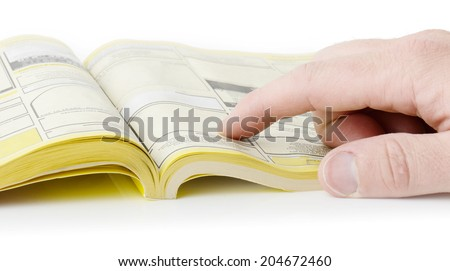 yellow pages searching with finger, blank spaces for text input. all information burred  - stock photo