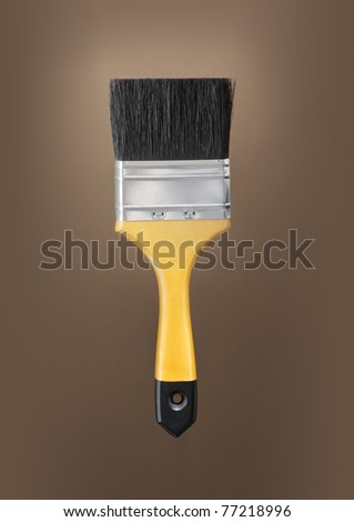 Yellow paint brush on brown background