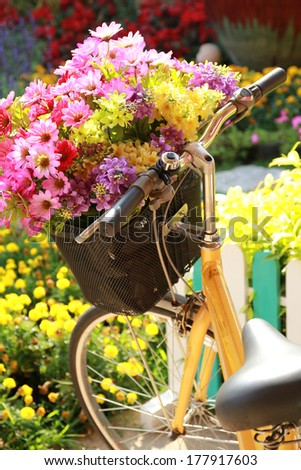 Yellow painted bicycle with a bucket of colorful flowers