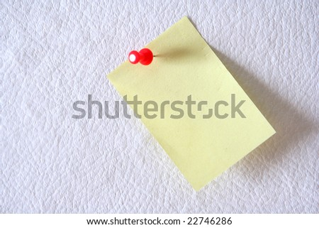 Yellow paper attached by the red button on a white background - stock photo