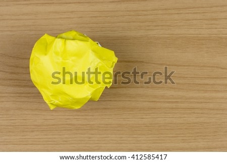 yellow paper ball on wood table.