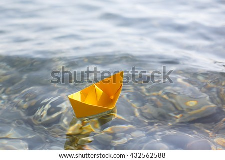 Yellow paper boat sailing on blue water surface - stock photo
