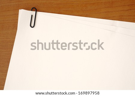Yellow paper clip attached to multiple sheets of paper - stock photo