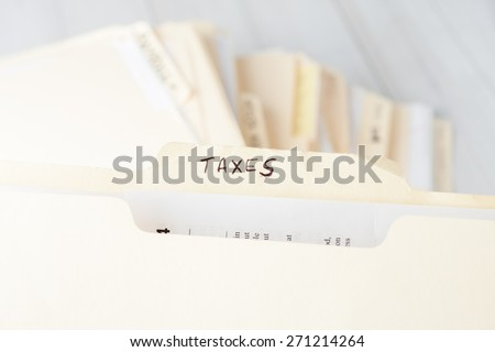 yellow paper folder labeled TAXES containing tax documents of a small business firm - stock photo
