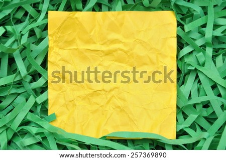 Yellow paper note on green shredded paper  - stock photo