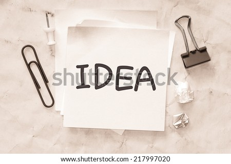 Yellow paper note with the words idea on white background with office stuff - stock photo