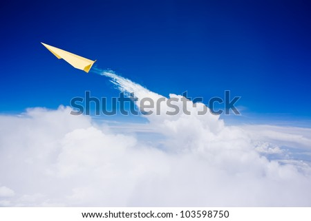 Yellow paper plane flying over clouds against blue sky - stock photo