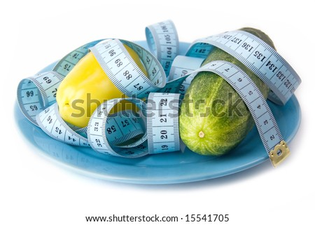 yellow paprika and green cucumber on plate with measure tape