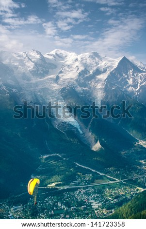 Yellow paraglide over village in Alps green valley - stock photo