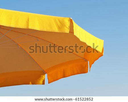 yellow parasol abstract isolated against clear blue sky - stock photo
