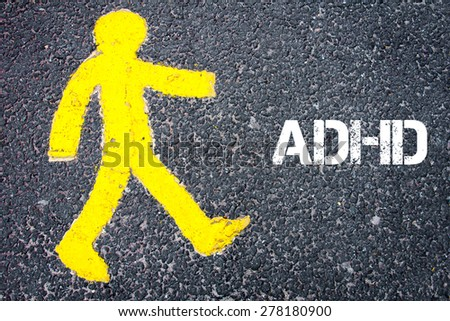 Yellow pedestrian figure on the road walking towards ADHD. Conceptual image with Text message over asphalt background.