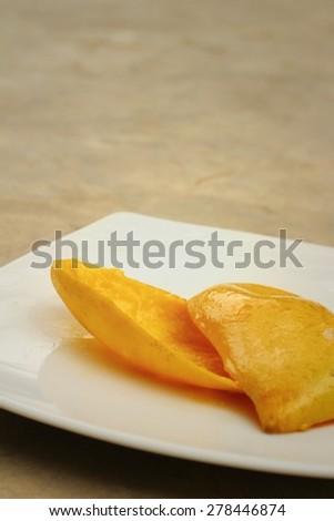 yellow peel mango on a white plate. - stock photo