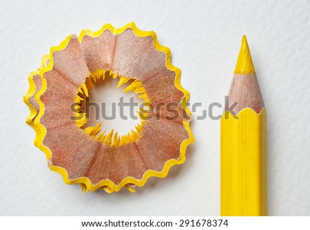 yellow pencil and shavings on white paper background - stock photo