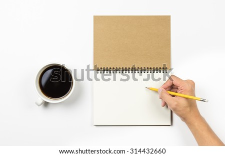 yellow pencil in hand write something on note book brown cover and black coffee cup with white background.