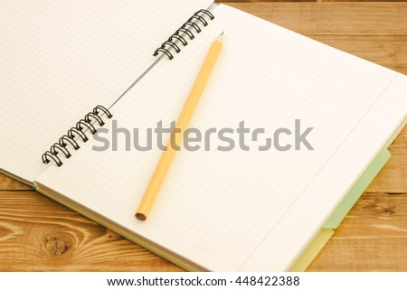 yellow pencil on notebook with bookmarks lying on a wooden table