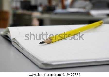 Yellow pencil on the notebook.