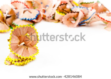 Yellow pencil shavings with more shavings at the background. Horizontal image.