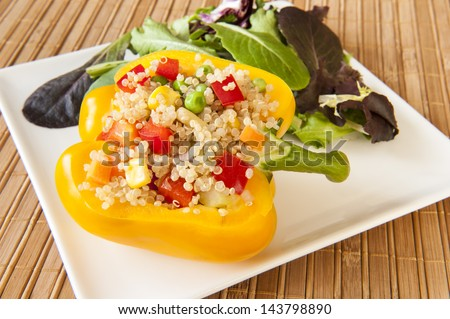Yellow pepper stuffed with quinoa and mixed vegetables with green salad - stock photo