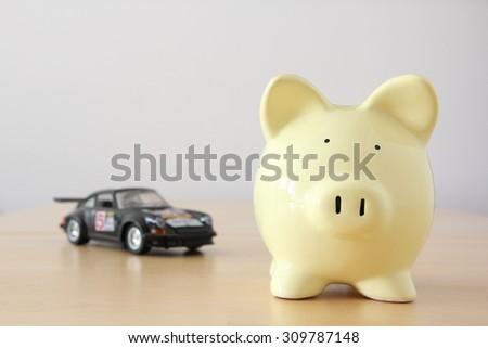 Yellow piggy bank on bright background, savings on car. - stock photo