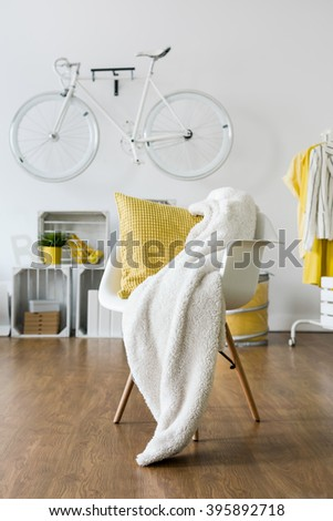 Yellow pillow and white blanket left on white armchair in lounge - stock photo