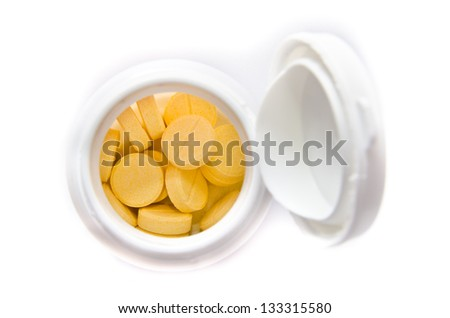 yellow pills in container isolated on a white background