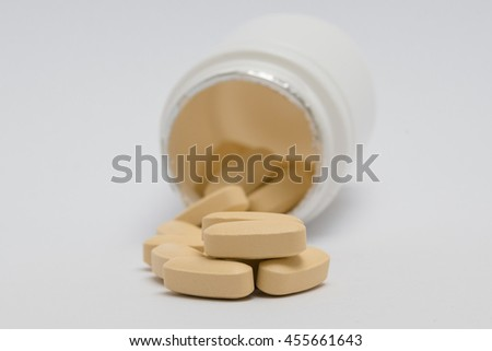 Yellow pills spilling out of pill bottle. Isolated on white background