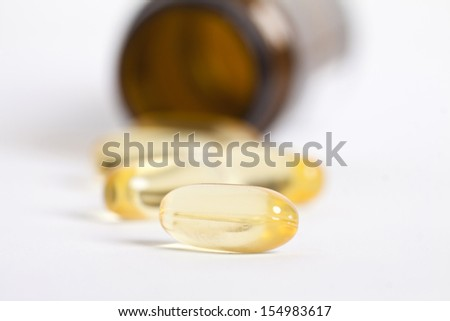 Yellow pills with pill bottle in the background
