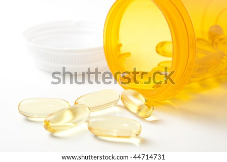 Yellow Pills with Prescription Bottle. Focus on pills directly in front of bottle.