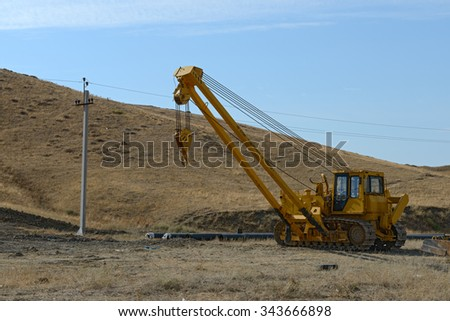Yellow pipe layer dozer is at pipeline building place in eastern Crimea.