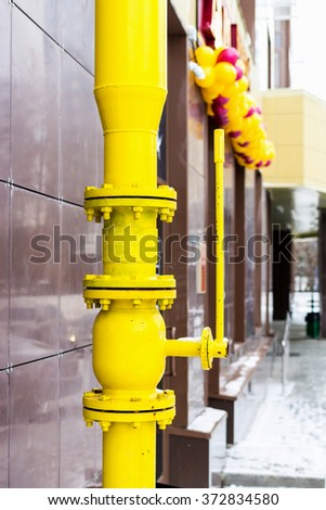 Yellow pipe on the facade of the building