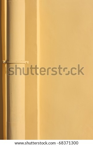 Yellow pipe on the yellow wall - stock photo